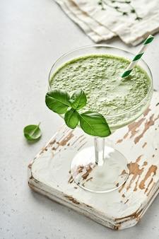 Detox grüner gemüsesaft oder smoothie, garniert mit frischem basilikum im cocktailglas auf hellgrauem schiefer-, stein- oder betonhintergrund. draufsicht mit kopienraum.
