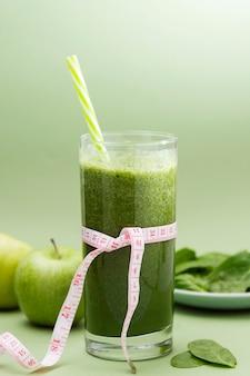 Detox grünes smoothieglas für loses wiegen und nähren, grüner hintergrund. gesundes essen.