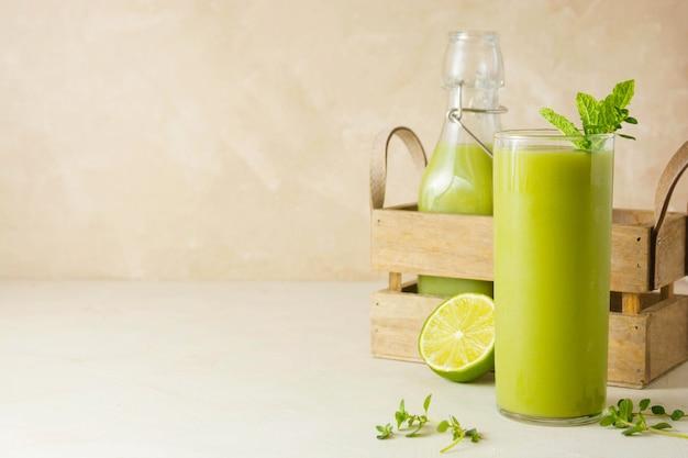 Detox-konzept. gesundes smoothie-glas mit frischem spinat, banane, ananas. köstliches hausgemachtes grünes getränk. platz kopieren