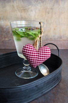 Detox minzgetränk und herzförmiges dekor als getränkekonzept für die valentinstagfeier