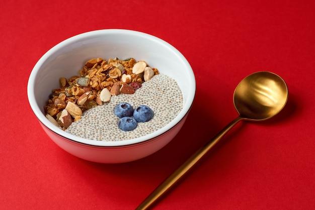 Detox und gesunde superfoods frühstücksschüssel konzept. veganer kokosmilch-chiasamen-pudding, blaubeeren und nüsse. oben, draufsicht, flach liegen.