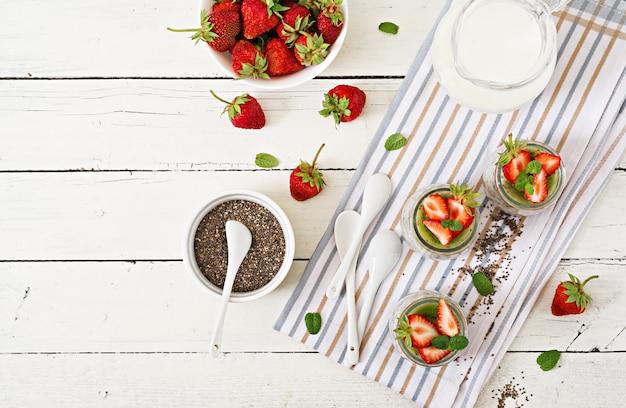 Detox und gesundes superfoods frühstück im glas. chia-samenpudding der veganen kokosmilch mit erdbeeren und kiwi. ansicht von oben. flach liegen.