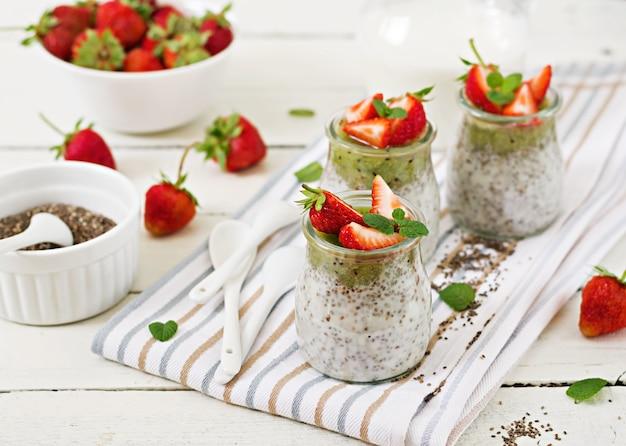 Detox und gesundes superfoods frühstück im glas. chia-samenpudding der veganen kokosmilch mit erdbeeren und kiwi.