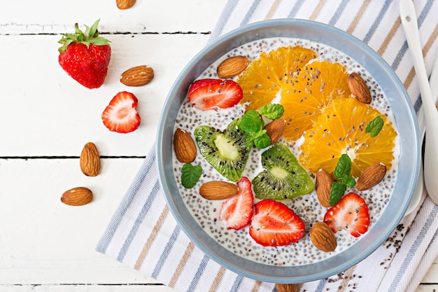 Detox und gesundes superfoods frühstück in der schüssel. chia-samenpudding der veganen mandelmilch mit erdbeeren, orange und kiwi. ansicht von oben. flach liegen