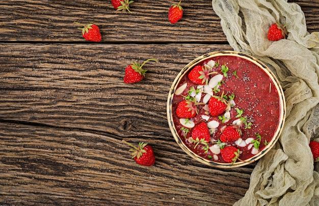 Detox und gesundes superfoods frühstück in der schüssel. veganer chiasamenpudding mit erdbeeren und mandel. erdbeer-smoothie. ansicht von oben. flach liegen