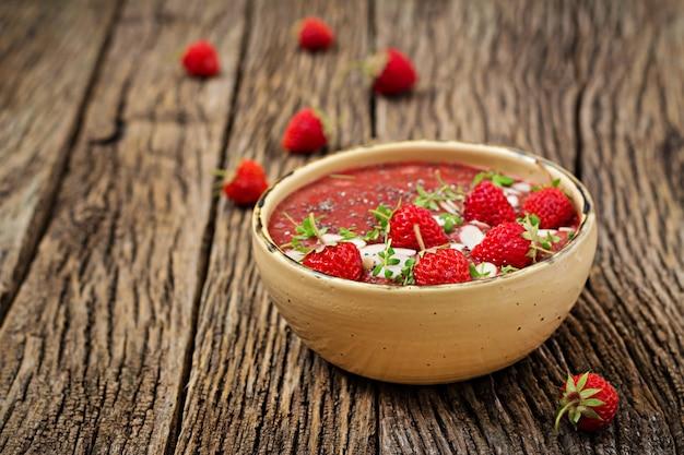 Detox und gesundes superfoods frühstück in der schüssel. veganer chiasamenpudding mit erdbeeren und mandel. erdbeer-smoothie.