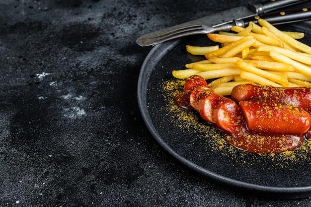 Deutsche currywurst würstchen mit pommes frites auf einem teller. schwarzer hintergrund. ansicht von oben. platz kopieren.