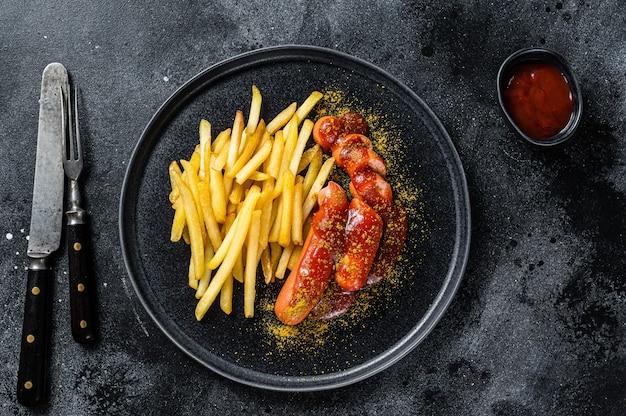 Deutsche currywurst würstchen mit pommes frites auf einem teller. schwarzer hintergrund. ansicht von oben.