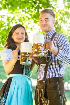 Deutsche paare in trinkendem bier tracht