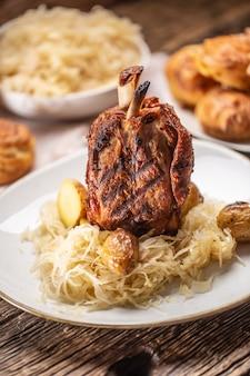 Deutsche schweinshaxe mit sauerkraut und ofenkartoffeln.