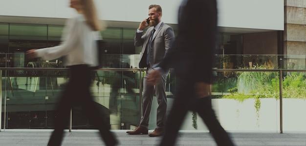 Deutscher geschäftsmann, der an einem telefon und an den leuten geht an ihm geht