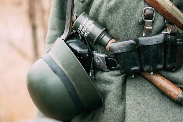 Deutscher helm am gürtel eines soldaten des zweiten weltkriegs