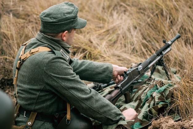 Deutscher soldat mit einem maschinengewehr im graben