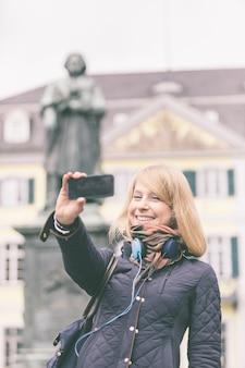Deutsches mädchen, das selfie in bonn-hauptplatz nimmt