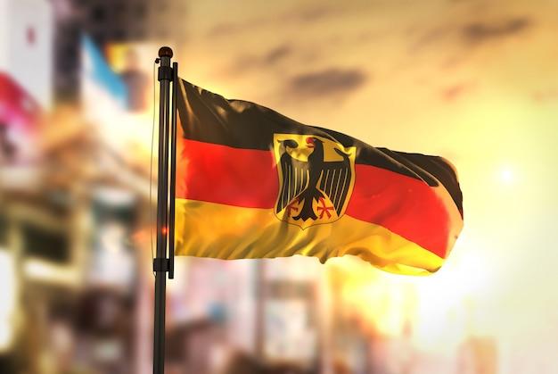 Deutschland flagge gegen stadt verschwommen hintergrund bei sonnenaufgang hintergrundbeleuchtung