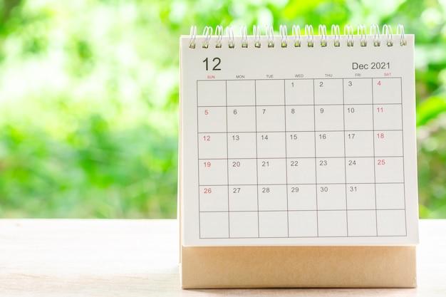 Dezember-monat, kalendertisch 2021 für organisatoren zur planung und erinnerung auf holztisch mit grünem naturhintergrund.