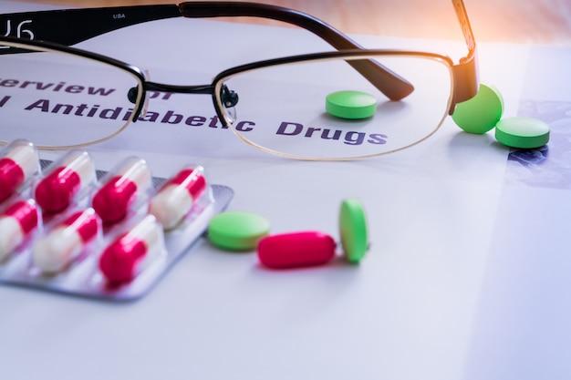 Diabetes drogen und gläser auf lehrbuch gelegt. diabetes mellitus typ 2 konzept.