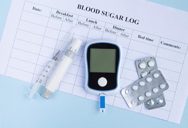 Diabetes-glukosemessgerät zur diagnose lanzettenspritze und pillen auf blutzuckerspiegelprotokoll draufsicht
