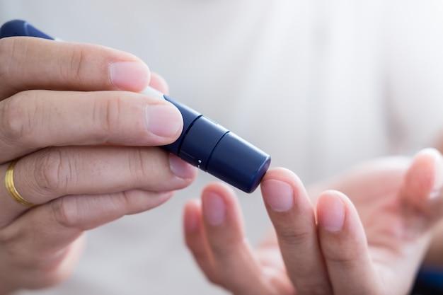 Diabetes, glykämiekonzept - mannhände verwenden lanzette am finger zur überprüfung des blutzuckerspiegels.