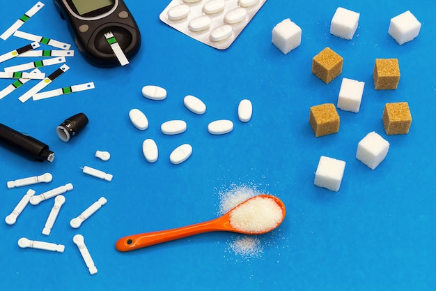 Diabetes mellitus. würfelzucker, ein teelöffel mit streuselzucker, ein glukometer mit teststreifen, ein fingerabdruckmessgerät zur blutzuckermessung
