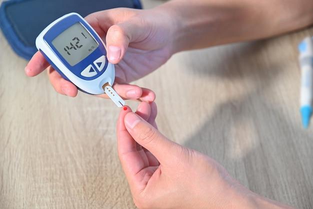 Diabetes-patienten verwenden ein zucker-blutzuckermessgerät, um ihren blutzuckerspiegel zu hause zu messen