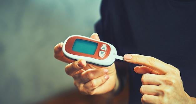Diabetikerin mit blutzuckermessgerät, weibliche hände halten lanzettenstift-glukometer am finger messen zucker-check-insulin