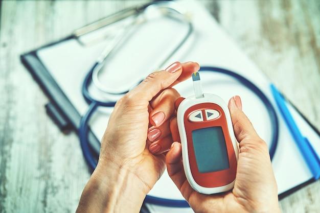 Diabetische frau mit blutzuckermessgerät, weibliche hände halten lanzettenstift-glukometer am finger messen zucker-check-insulin
