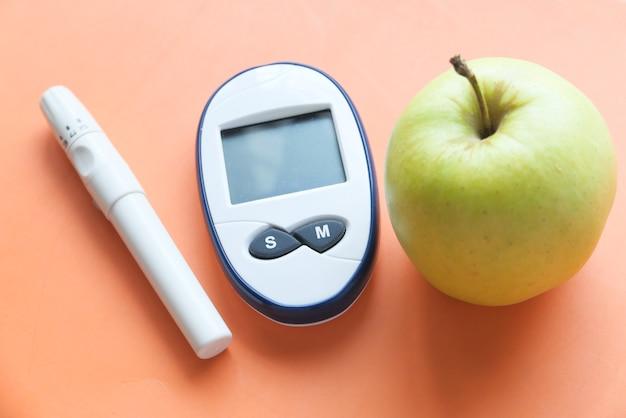 Diabetische messwerkzeuge apfel auf orange hintergrund