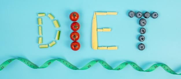 Diät-arrangement von obst und gemüse; blaubeeren, kirschtomaten, gurken und babymais auf blauem hintergrund. gewichtsverlust, ernährung, gesunde ernährung, intermittierendes fasten und vegetarisches konzept