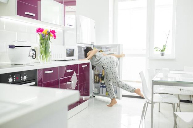 Diät-betrüger. frau in der küche in der nähe des kühlschranks. frau möchte essen. hungrige frau am morgen.