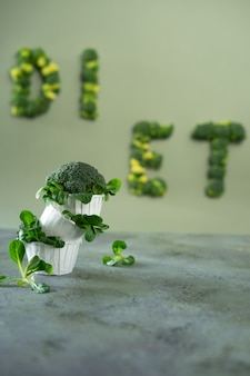 Diät-cupcake aus brokkoli und maissalat. word-diät aus brokkoli beschriftet. lebensmittel-schriftzug