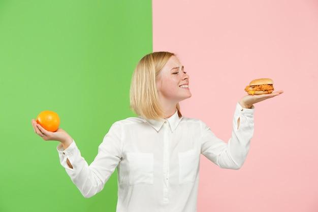 Diät. diätkonzept. gesundes essen. schöne junge frau, die zwischen früchten und unhelathischem fast food wählt