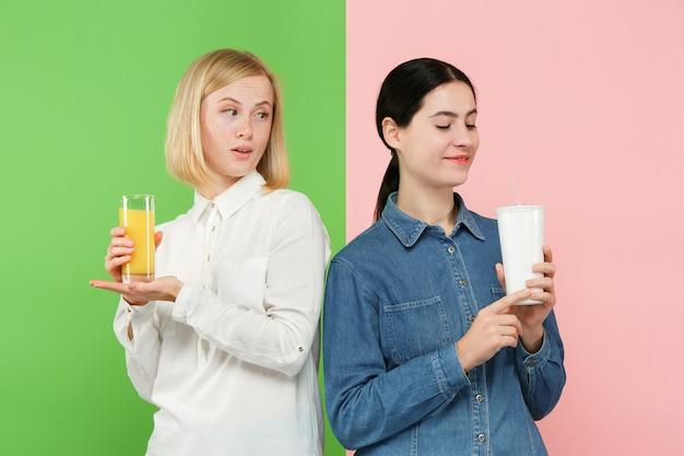 Diät. diätkonzept. gesundes essen. schöne junge frauen, die zwischen fruchtorangensaft und unhelathischem kohlensäurehaltigem süßem getränk wählen