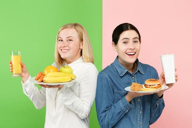 Diät. diätkonzept. gesundes essen. schöne junge frauen, die zwischen früchten und unhelathischem fast food wählen