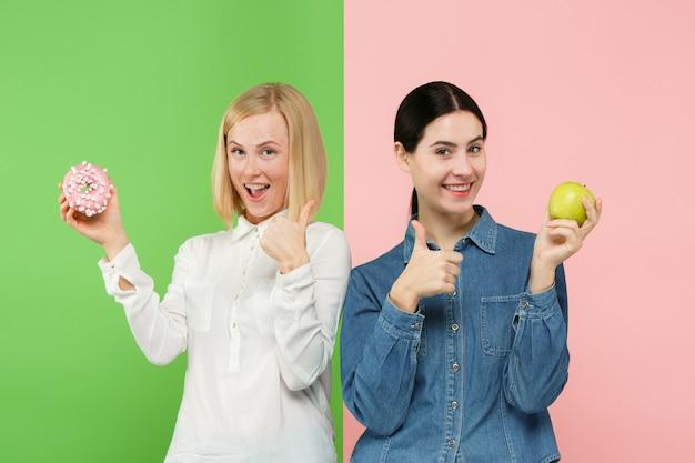 Diät. diätkonzept. gesundes essen. schöne junge frauen, die zwischen früchten und unhelathy-kuchen wählen