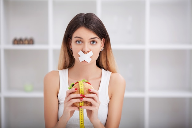 Diät. die von gesunder und ungesunder ernährung. das modell plus size entscheidet sich für gesundes essen und obst, indem es auf fast food und burger verzichtet. xxl frau
