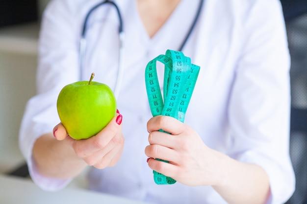 Diät. eignung und gesundes lebensmitteldiätkonzept. ausgewogene ernährung mit gemüse. porträt des netten doktorernährungswissenschaftlers, der grünen apfel misst. konzept der natürlichen nahrung und des gesunden lebensstils.