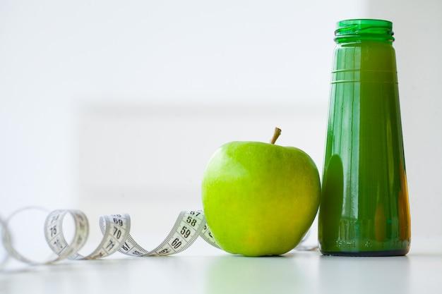 Diät. eignung und gesundes lebensmitteldiätkonzept, grüner saft. frisches obst und glaswasser, messendes band auf weißem hintergrund. nahansicht