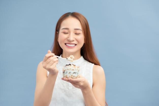 Diät-ernährungskonzept. hübsches mädchen mit joghurt, rosinen und haferflocken