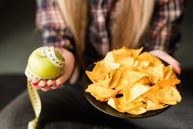 Diät essen gegen fast food. frau hält apfel und teller mit pommes in händen. gesunde lebensgewohnheiten