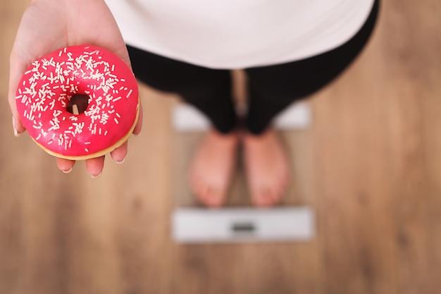 Diät, frau, die körpergewicht auf der waage hält donut misst