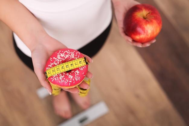 Diät, frau, die körpergewicht auf der waage hält donut und apfel misst