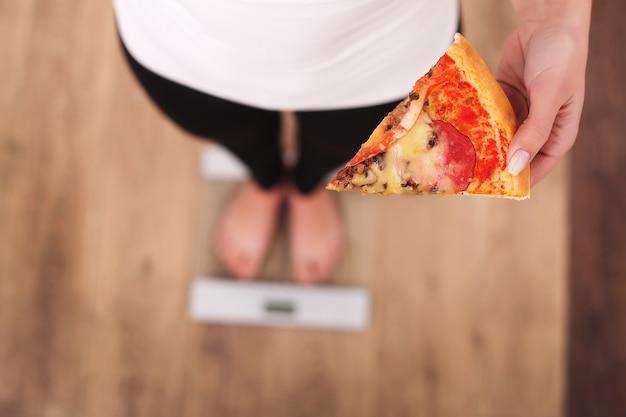 Diät, frau, die körpergewicht auf der waage hält pizza misst