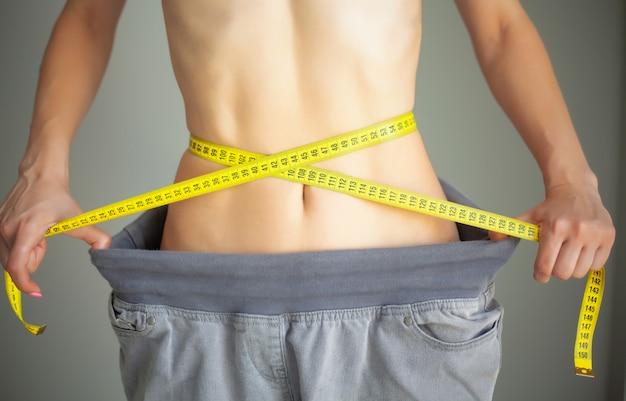 Diät. frau in der sportkleidung, die ihre taille misst. abnehmen