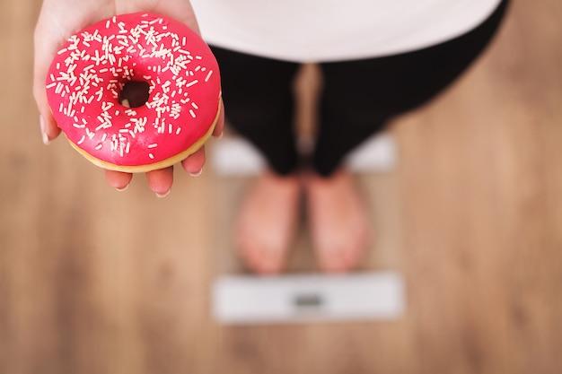 Diät. frauen-messendes körpergewicht auf der waage, die donut hält.