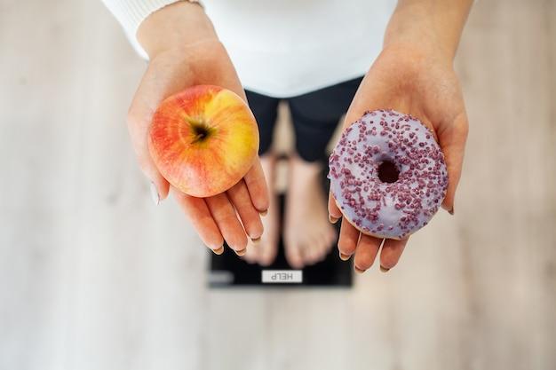 Diät. frauen-messendes körpergewicht auf der waage, die donut und apfel hält. süßigkeiten sind ungesunde junk-food. abnehmen, gesunde ernährung, lebensstil. gewichtsverlust. fettleibigkeit. ansicht von oben