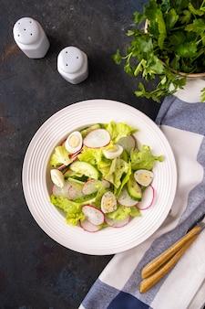 Diät gemüsesalat mit gurken, quaill-eiern und radieschen auf einem weißen teller. draufsicht.