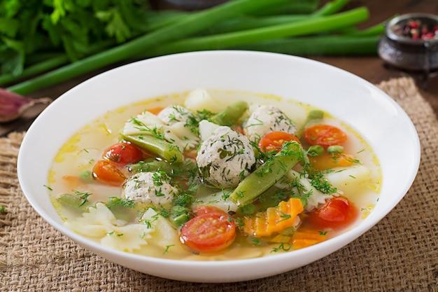 Diät gemüsesuppe mit hühnerfleischbällchen und frischen kräutern in holzschale