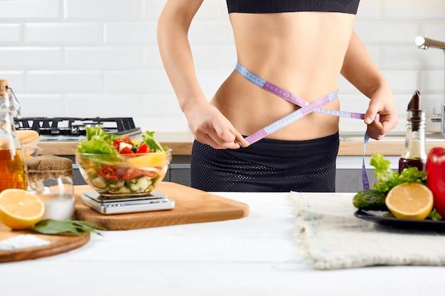 Diät, gesunde ernährung, essen und gewichtsverlust konzept. junge frau, die taille nahe tomaten, paprika und salat auf dem kücheninnenraum misst.