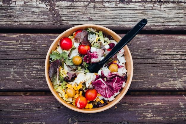 Diät griechischer salat mit feta, tomaten. gesundes mittagessen. lieferung von lebensmitteln in einweg-teller aus kraftpapier.
